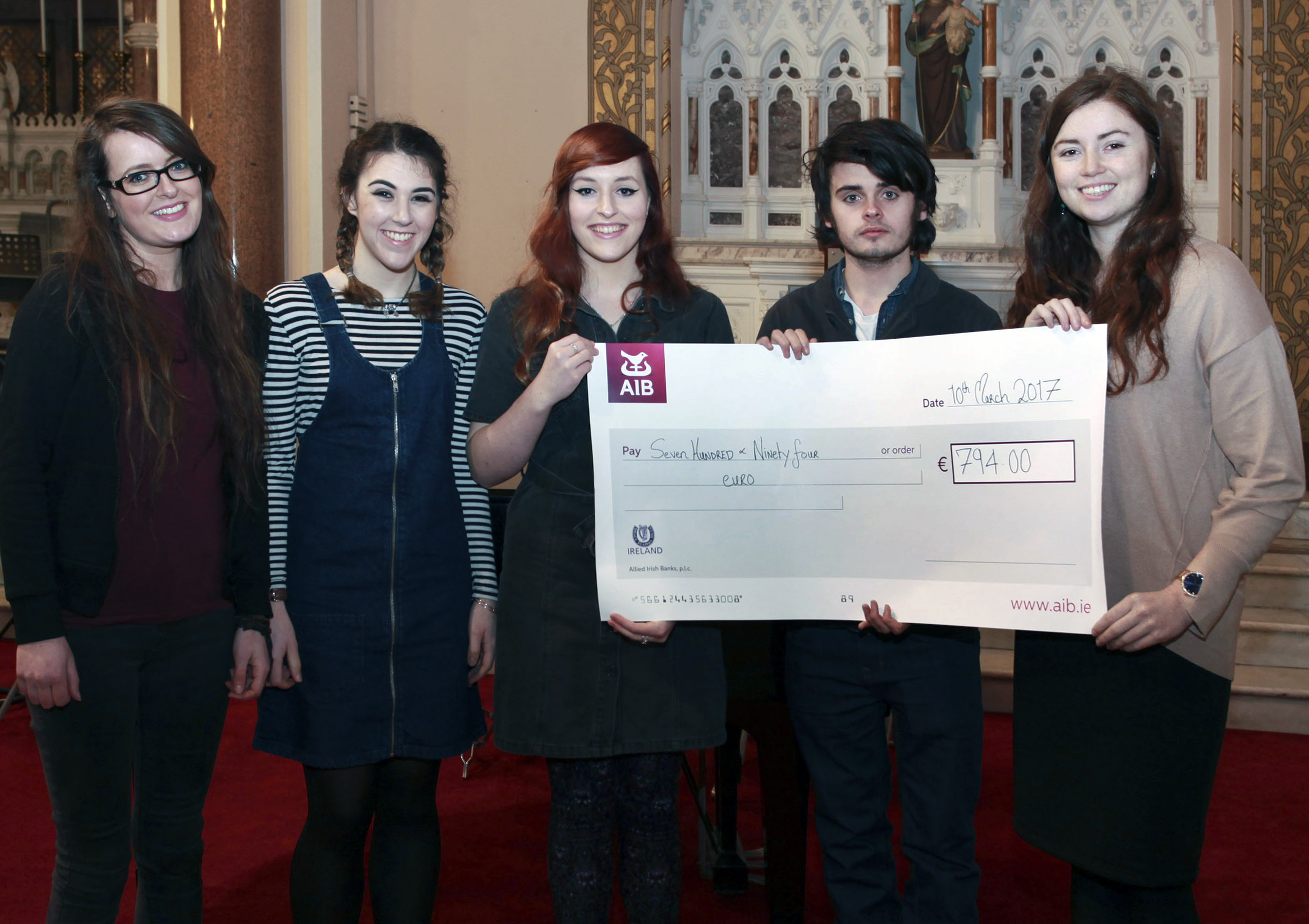 From Left: Students Emer Quilty,  Heather McGrath,  Emma Power, Tramore; and Killian Browne giving a cheque to Margaret Coleman, Focus Ireland Waterford