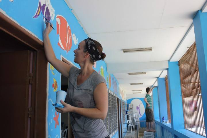 Visual arts student, Emma Ryan at the Nano Badjao school in the Philippines painting a mural